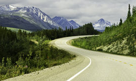 Asphalt road in high mountains of Alaska Stock Photos