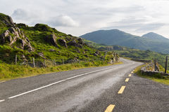Asphalt road and hills at connemara in ireland. Travel, trip and countryside concept - view to asphalt road and rocky hills at connemara in ireland Royalty Free Stock Photography
