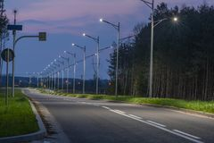 Asphalt Road In The Evening Light, Illuminated With The Light Of Street Lanterns. Stock Photos