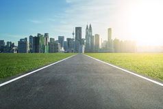 Asphalt road leading to a city. With tall buildings through green meadow Royalty Free Stock Photo