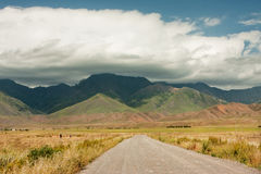 Asphalt road leading to the high mountains covered by thunderclouds before rain Royalty Free Stock Photography