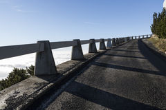 Asphalt road leads to the mountain peak, sunny day, blue sky Stock Photos