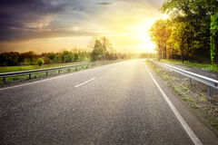 Asphalt road leaving for turn to the sun Royalty Free Stock Image