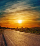 Asphalt road and low sun in dramatic clouds Royalty Free Stock Photography