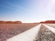 Asphalt road with marking. Toning. The picturesque landscape and the Sunrise over the road. Asphalt road with marking. With the blur Royalty Free Stock Photo