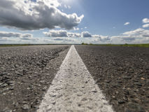 Asphalt, road markings and sky with clouds. Conceptual background in the style of Traveling or Logistics. Horizontal Royalty Free Stock Photography