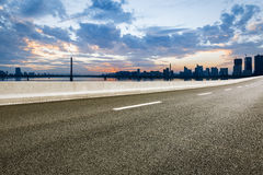 Asphalt road and modern city skyline at sunset Royalty Free Stock Image