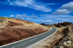 Asphalt road. Mountain asphalt road, cut through red ground, band ind the road and blue sky with some clouds Royalty Free Stock Photo