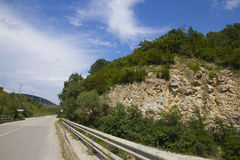 Asphalt road in mountains. Against the blue sky with white clouds Stock Photo