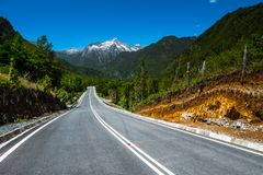 Asphalt road with mountains. On the background. Adventure road Carretera Austral Ruta N7 near the town of Hornopiren, Chile stock photography
