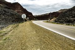 Asphalt road between mountains, distant routes that curve into new places. Trips to the unknown. stock photography