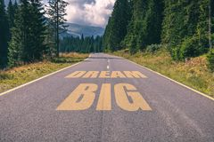 Asphalt road in the mountains going straight up with dream big t royalty free stock image