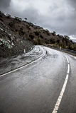 Asphalt road in the mountains. Winter. Rain. Toned Stock Photos