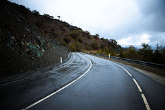 Asphalt road in the mountains. Winter. Rain. Toned Stock Image
