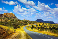 Asphalt road in Namibia. Gorgeous autumn turned yellow bush and mountains in the distance stock photos