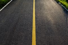 Asphalt Road. New asphalt road with yellow line before sunset Stock Photo