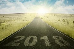 Asphalt road with numbers 2018. Image of empty asphalt road with numbers 2018 in the meadow Royalty Free Stock Photo
