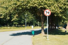 Asphalt road between old green trees at the park with a sign for. Bidden to walk with the dogs. Dogs not permitted not allowed in area sign Royalty Free Stock Image