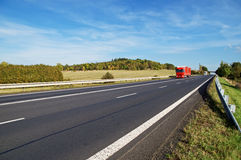 Asphalt road with oncoming trucks in countryside, early autumn colors Royalty Free Stock Images