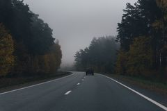 Asphalt road with one dark car, autumn trees and fog. Vintage,retro look. royalty free stock image