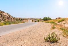 Asphalt Road ovanför tusen dollarkrater i den Negev öknen Arkivfoto