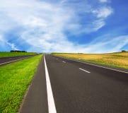 Asphalt road over blue sky Stock Images