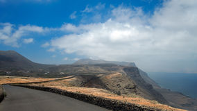 Asphalt road over a cliff above the ocean disappearing over the horizon through volcano mountain hillsides. White clouds on a blue Stock Photography