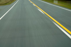 Asphalt road overpass motion blur. With white and yellow lines Stock Images