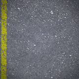 Asphalt road pavement with cracked yellow marking Stock Image