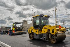 Asphalt road paver and road roller. Tyumen. Russia. Tyumen, Russia - June 1, 2017: JSC Mostostroy-11. Construction of two-level outcome on bypass road on Royalty Free Stock Photos