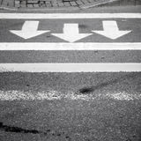 Asphalt road, pedestrian crossing marking. White arrows and lines on dark gray asphalt road, pedestrian crossing road marking Stock Images