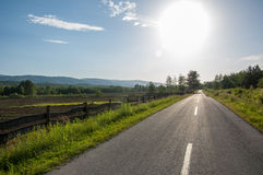 Asphalt road with plowed field and mountain Papuk in the backgro Royalty Free Stock Photo