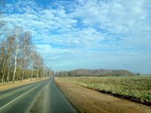 Asphalt road in retro style through the fields and forests against the blue sky with lush clouds stock images