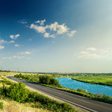 Asphalt road and river under sunset in blue sky Stock Photo