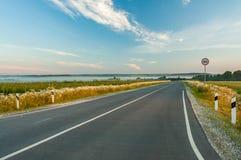 Asphalt Road With Road Sign unter blauem drastischem Himmel Stockfotografie