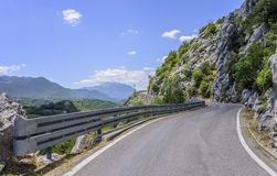 An asphalt road in the rocky mountains near the byss. Stock Images