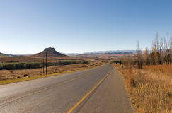 Asphalt Road Running Through Dry Winter Landscape in South Afric. Long straight empty rural asphalt road running through dry winter landscape against blue sky Royalty Free Stock Images