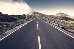 Asphalt road running at the foot of the volcano Royalty Free Stock Image