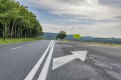 Highway passing near the beech forest in the evening time. Asphalt road running near beech forest with road signs. English translation of Romanian road Caution stock images