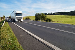 Asphalt road in a rural landscape. The arriving two white trucks on the road. Stock Images