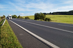 Asphalt road in a rural landscape. The arriving white truck on the road. Stock Photography