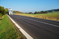 Asphalt road in a rural landscape, two truck Royalty Free Stock Photography