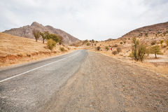 Asphalt road in a sandy valley among the mountains Royalty Free Stock Photography