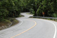 Asphalt road sharp curve along with tropical forest Stock Image
