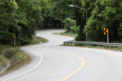 Asphalt road sharp curve along with tropical forest Royalty Free Stock Image