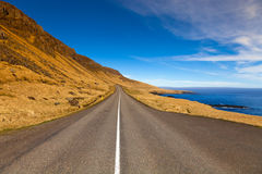 Asphalt road on the shore of the fjord in the east of Iceland Stock Images