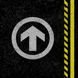 Asphalt road sign. Black grunge asphalt with yellow lines and white arrow sign Royalty Free Stock Photo
