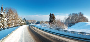 Asphalt road in snowy winter on beautiful sunny day Royalty Free Stock Photo