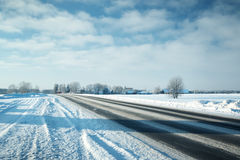Asphalt road in snowy winter on beautiful sunny day Stock Photo