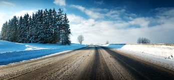 Asphalt road in snowy winter on beautiful sunny day Royalty Free Stock Photography